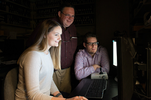 Julia Sunstrum, Stephen Lomber and Blake Butler examine images on a computer screen